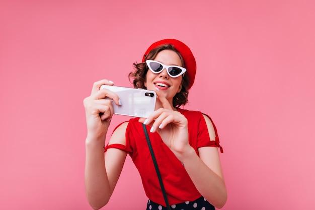 Señora francesa glamorosa en gafas vintage tomando una foto de sí misma. mujer rizada en boina roja haciendo selfie.