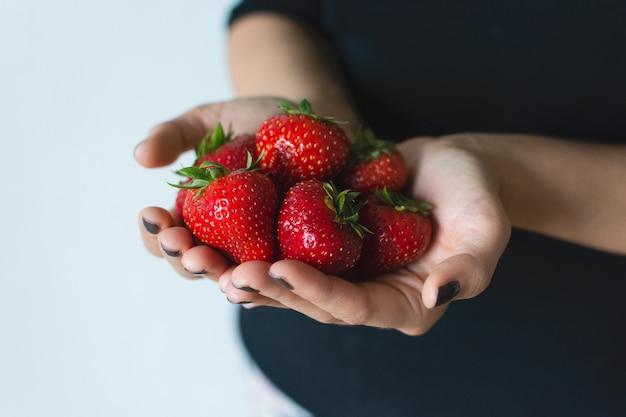Señora con fresas maduras frescas en sus manos