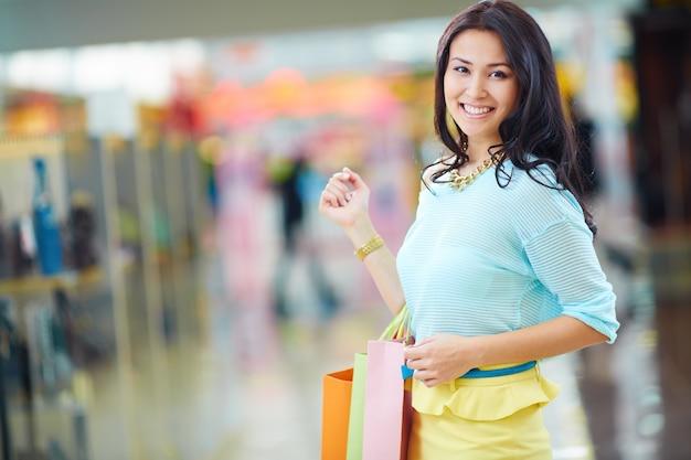 Señora con una gran sonrisa y bolsas de la compra