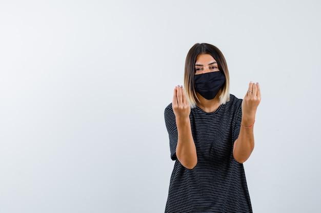 Señora haciendo gesto italiano en vestido negro, máscara médica y mirando cortés, vista frontal.