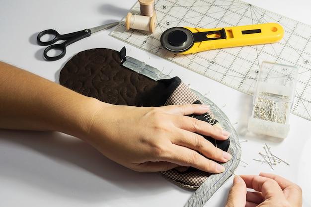 La señora está haciendo un zapato suave de tela hecho a mano.