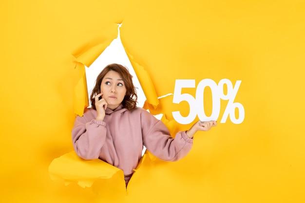 Señora hermosa joven que muestra el signo del cincuenta por ciento y se siente sorprendido sobre el fondo amarillo de la sequía desgarrada