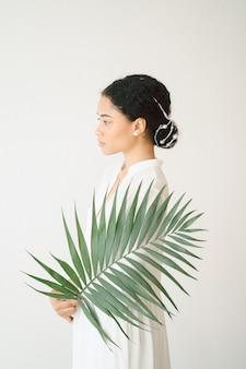 Señora hermosa que coloca y que sostiene la rama de palma en vestido blanco largo en sitio vacío.