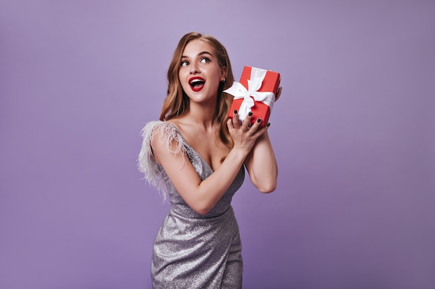 Señora con hermoso maquillaje con caja de regalo en la pared púrpura