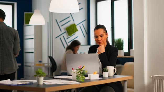 Señora hispana feliz escribiendo en la computadora portátil sentado en el escritorio en la puesta en marcha de la oficina de negocios tomando café mientras diversos colegas trabajan en segundo plano. compañeros de trabajo multiétnicos que planifican un nuevo proyecto financiero.