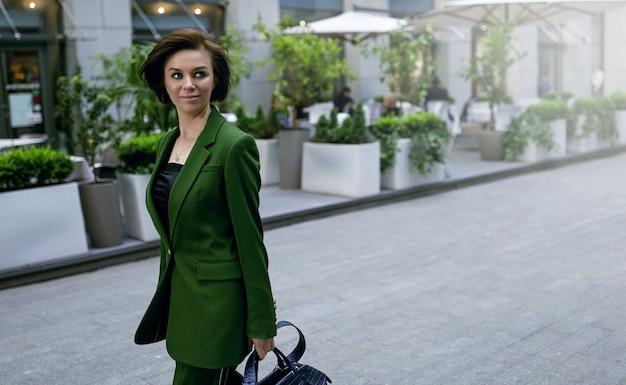 Señora independiente caminando por la calle, sosteniendo su bolso. chaqueta verde de moda en ella. corte de pelo corto y sexy, seguro e inteligente.
