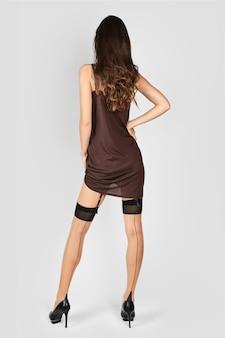 Señora irreconocible levantando vestido y mostrando medias y liguero