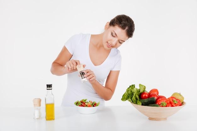 Señora joven alegre cocinar con verduras y aceite