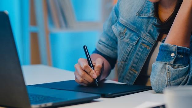 Señora joven alegre del diseñador gráfico que usa la tableta gráfica digital mientras que trabaja tarde en la oficina moderna en la noche, hembra profesional de asia que usa el retocador de la computadora portátil que se sienta en sala de estar en casa.