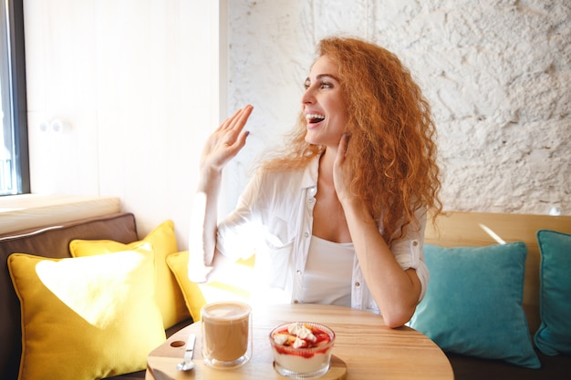 Señora joven alegre del pelirrojo que se sienta en café mientras que come el postre.
