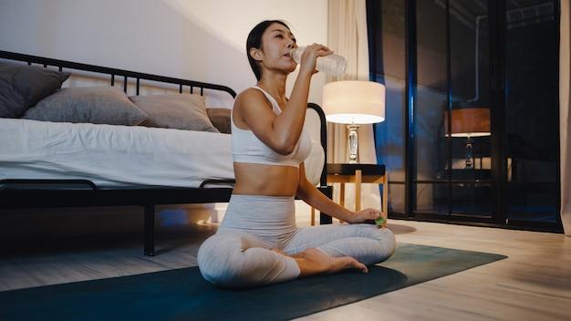 Señora joven de asia haciendo ejercicio de yoga trabajando y bebiendo agua pura en la sala de estar en casa por la noche.