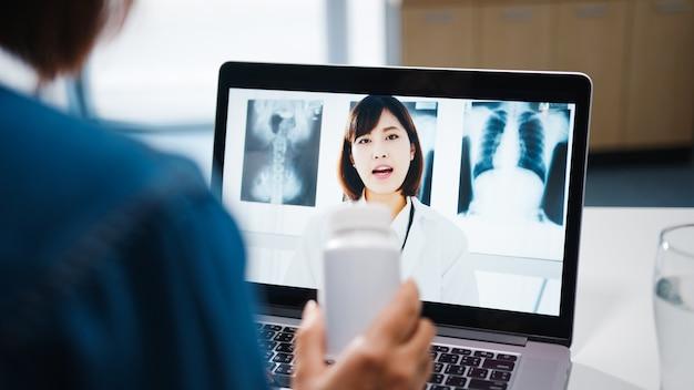 Señora joven de asia que usa la computadora portátil hablar sobre una enfermedad en la llamada de videoconferencia con la consulta en línea del médico senior en la sala de estar en casa