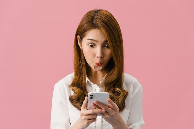 Señora joven de asia que usa el teléfono con expresión positiva, sonríe ampliamente, vestida con ropa casual sintiendo felicidad y de pie aislado sobre fondo rosa.