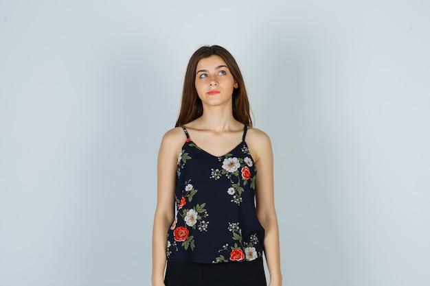 Señora joven atractiva en blusa mirando hacia arriba y mirando pensativo, vista frontal.