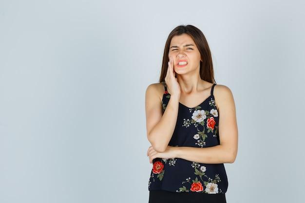 Señora joven atractiva en blusa que sufre de dolor de muelas terrible y mirando molesto, vista frontal.