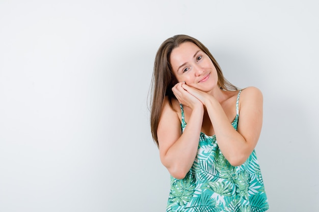 Señora joven en blusa que acolcha la cara en sus manos y mira soñolienta, vista frontal.