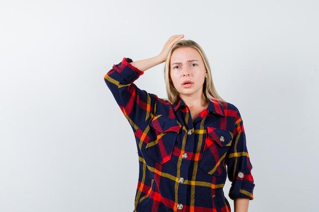 Señora joven en camisa a cuadros sosteniendo la mano en la cabeza y mirando perplejo, vista frontal.