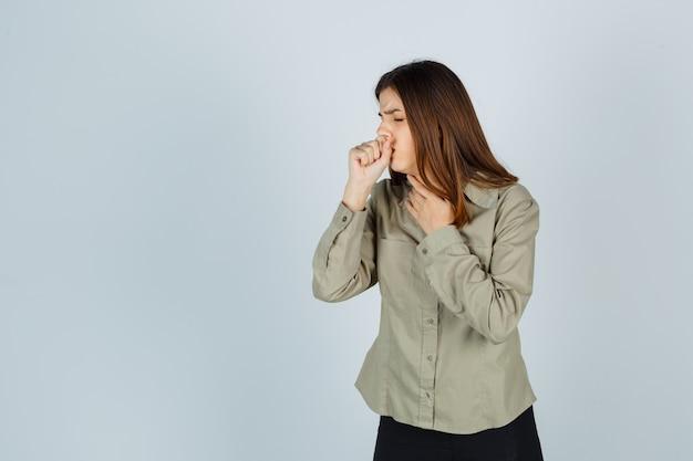 Señora joven en camisa, falda que sufre de tos y parece enferma, vista frontal.