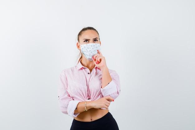 Señora joven en camisa, máscara manteniendo la mano en la barbilla y mirando pensativo, vista frontal.