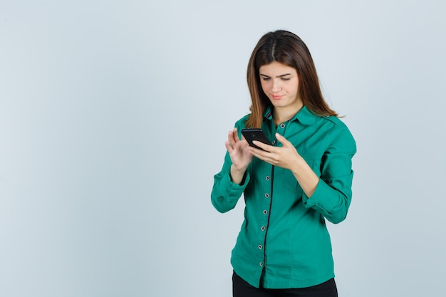Señora joven en camisa verde escribiendo en el teléfono móvil y mirando ocupado, vista frontal.