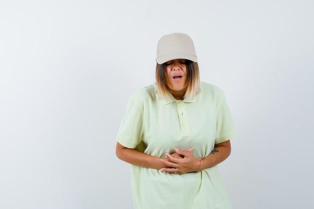 Señora joven en camiseta, gorra que sufre de dolor de estómago y parece enferma, vista frontal.