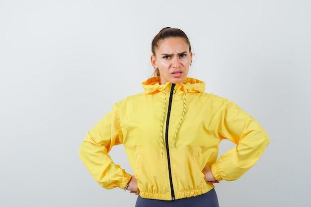 Señora joven en chaqueta amarilla con las manos en la cintura y mirando enojado, vista frontal.