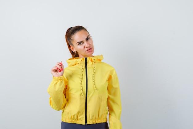 Señora joven en chaqueta amarilla posando y mirando confiado, vista frontal.