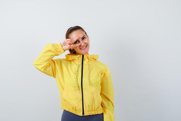 Señora joven en chaqueta amarilla que muestra el signo de la victoria en el ojo y mirando alegre, vista frontal.