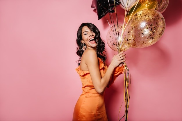 Señora joven complacida en vestido naranja expresando felicidad