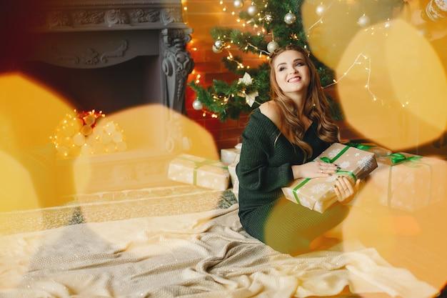 Señora joven elegante que se sienta cerca del árbol de navidad