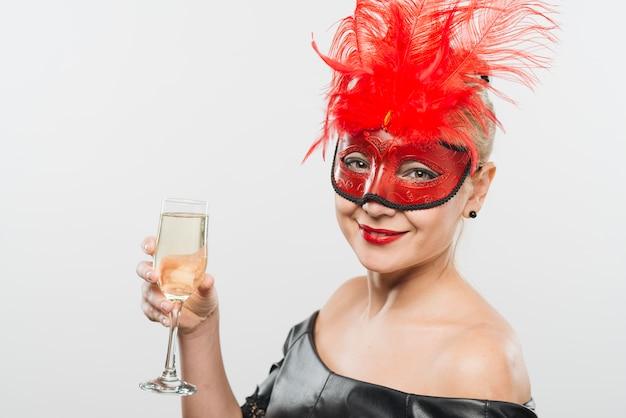 Señora joven feliz en máscara con las plumas rojas que sostienen el vidrio