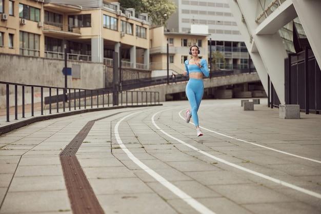 Señora joven en forma está haciendo fitness y trotar en un lugar urbano
