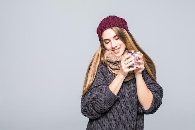 Señora joven con gripe y bebidas frías, bebida caliente, té herbal para estar saludable en gris
