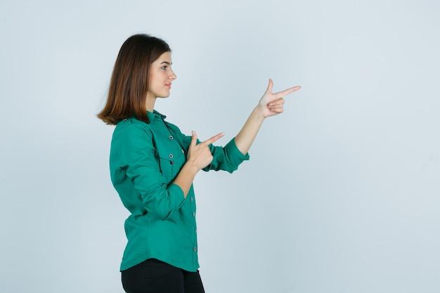 Señora joven hermosa que muestra el gesto del arma en camisa verde y que parece confiada. .