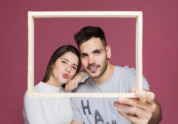 Señora joven con la mano en el hombro del individuo positivo que sostiene el marco de la foto