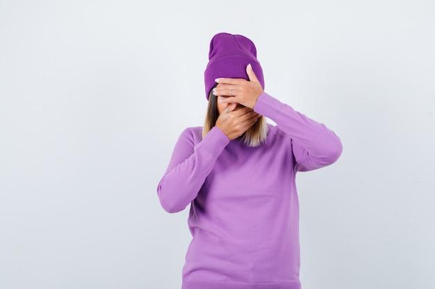 Señora joven con las manos en la cara en suéter morado, gorro y con cara de tristeza. vista frontal.