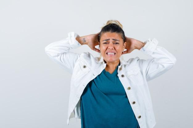 Señora joven con las manos detrás de la cabeza en camisa, chaqueta blanca y mirando ansiosa. vista frontal.