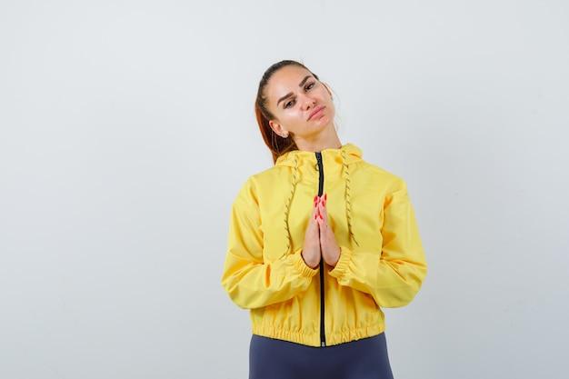 Señora joven con las manos en gesto de oración en chaqueta amarilla y mirando esperanzado. vista frontal.