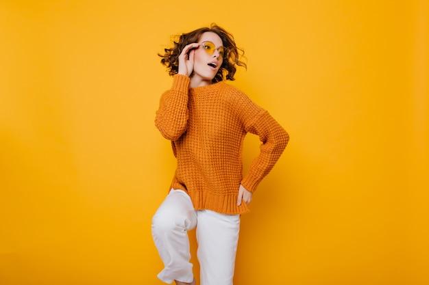 Señora joven de moda en suéter de punto y pantalón blanco de pie sobre una pierna y mirando a otro lado con la boca abierta