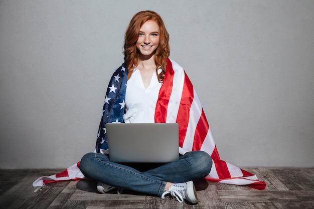 Señora joven pelirroja con bandera de estados unidos usando la computadora portátil