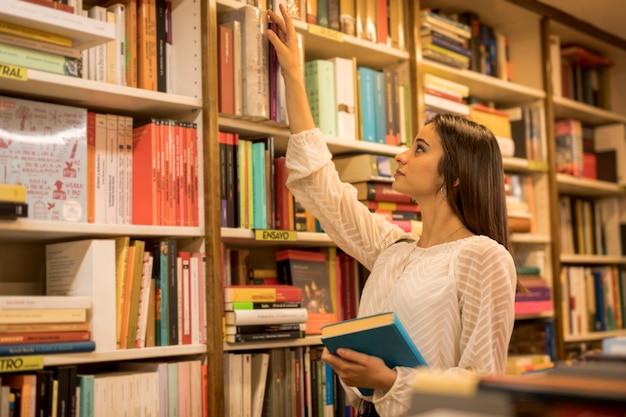 Señora joven que elige el libro en biblioteca