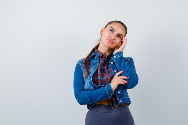 Señora joven que se inclina la cabeza en la mano en camisa a cuadros, chaqueta de mezclilla y mirando pacífica, vista frontal.