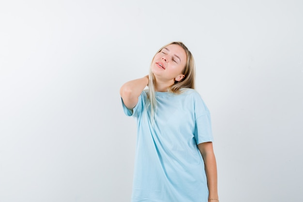 Señora joven que lleva a cabo la mano en el cuello en camiseta y parece fatigado. vista frontal.