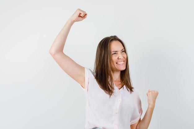 Señora joven que muestra el gesto del ganador en camiseta y parece feliz. vista frontal.