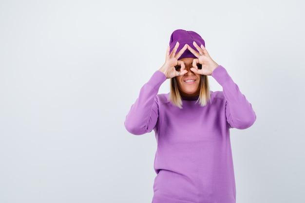Señora joven que muestra el gesto de los vidrios en suéter púrpura, gorro y que parece divertido. vista frontal.