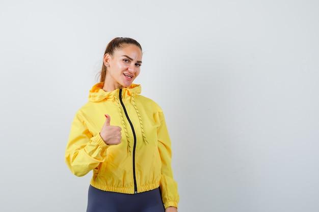 Señora joven que muestra el pulgar hacia arriba en la chaqueta amarilla y parece complacida. vista frontal.