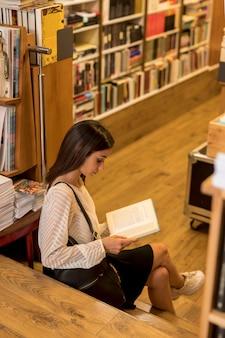 Señora joven que se sienta en las escaleras y el libro de lectura