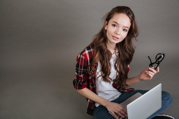 Señora joven que sostiene los vidrios que charlan por la computadora portátil.