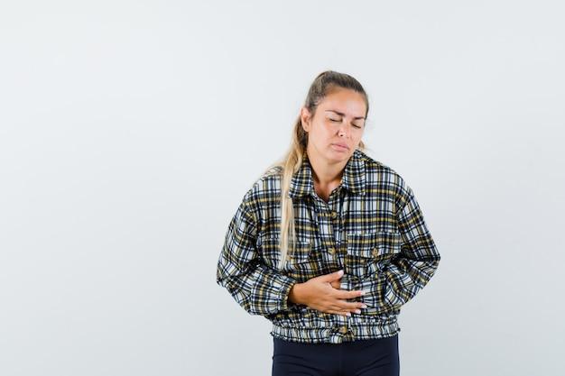 Señora joven que sufre de dolor de estómago en camisa, pantalones cortos y se ve mal. vista frontal.