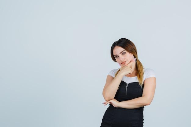 Señora joven rubia en vestido gesticulando aislado